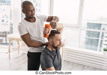 Professional male coach helping the patient