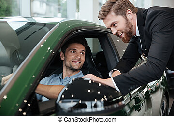 Professional male dealer selling car to a customer at the...