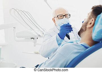 Professional male dentist diagnosing patient