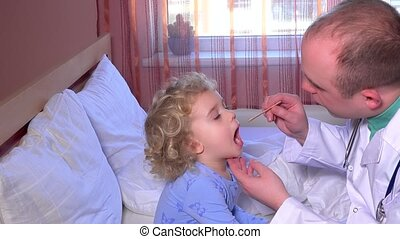 Professional male doctor checking his little patient girl throat sitting on bed
