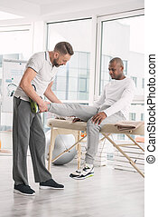 Professional male doctor examining patients leg
