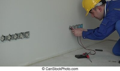 Professional male electrician using special tool to check wall socket voltage