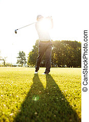 Professional male golf player hitting with a driver from a tee