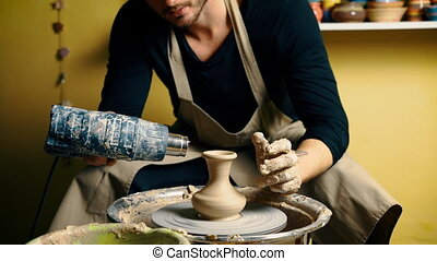 Professional male potter drying ceramic pot with special...