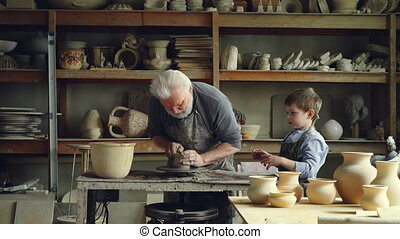 Professional male potter is working with clay on spinning...