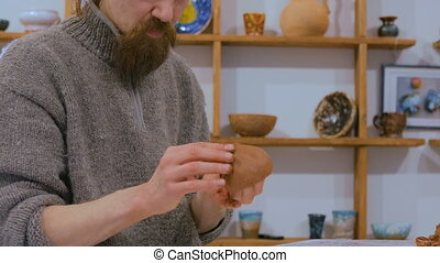 Professional male potter making ceramic jug in pottery...
