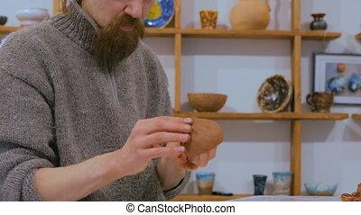 Professional male potter making mug in pottery workshop -...