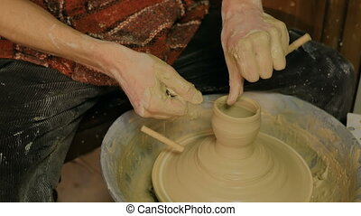 Professional male potter making mug in pottery workshop,...