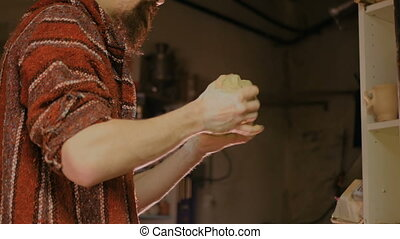 Professional male potter preparing clay for work