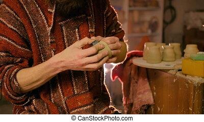 Professional male potter working in workshop, studio -...