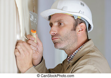 professional male stripping wallpaper with a scraper