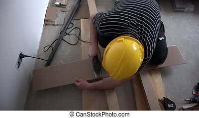 Professional male worker cutting laminate board with...