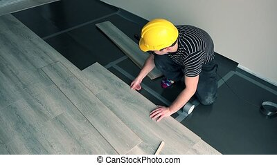 Professional male worker with yellow hard hat installing floor boards
