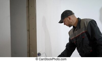 professional man in working form paints the walls in the apartment, the builder holds a roller in his hands