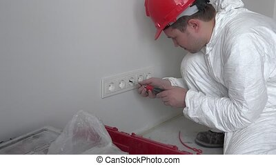 Professional man mount wall socket outlet on new flat house building apartment
