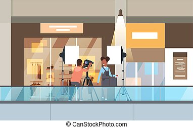 professional man photographer using dslr camera on tripod shooting african woman model girl posing in modern shoping mall supermarket interior horizontal full length
