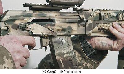 Professional man shooting from an assault rifle in a firing...
