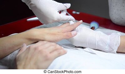 Professional manicure process, beautician trimming nails to...