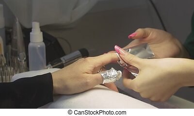 Professional manicurist wraps nails of woman by foil in beauty saloon. Nail shellac removal