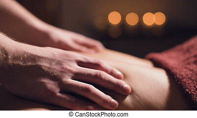 Professional massage of the back and lower back. Male masseur massages a client to a woman in a dark room by candlelight