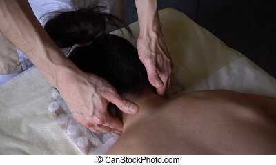 Professional Masseur Kneads the Neck of Young Woman With Warm Oil on at Massage Session. Ayurvedic Abyanga massage.