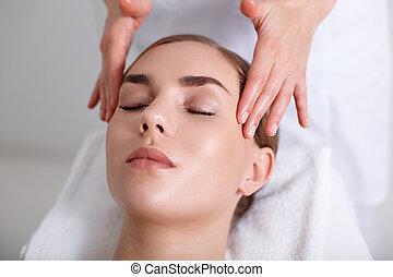 Professional masseuse massaging head of girl