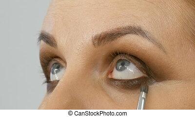 Professional master makeup artist applies beige eyeshadow...