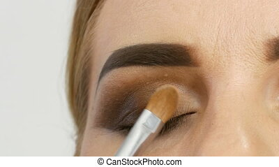 Professional master makeup artist applies beige eyeshadow...