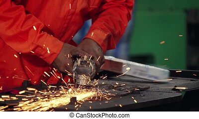 Professional mechanic is cutting steel metal with rotating diamond blade cutter. Steel industry and workshop concept.
