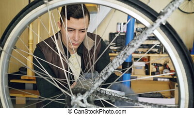 Professional mechanic man is repairing bicyce wheel in modern workplace with spare parts and special equipment. Maintenance, people and small business concept.