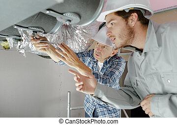 professional mechanic team repair air conditioning unit