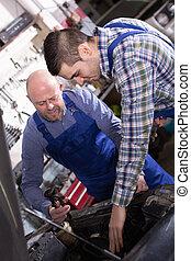 Professional mechanics repairing car