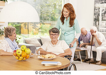 Professional medical caretaker in uniform helping smiling senior woman on a wheelchair in a living room of private luxury healthcare clinic. Elderly men and women inside a happy care home.