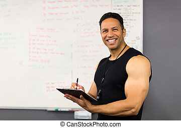 middle aged male trainer writing on clipboard