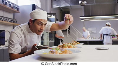 Professional mixed race male chef in a restaurant kitchen, ...