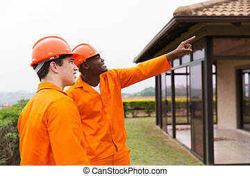 multiracial male construction workers pointing at house