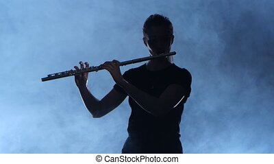 Professional musician female playing on flute. Smoky isolated studio, silhouette