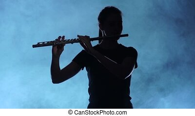 Professional musician female playing on flute. Smoky studio, slow motion