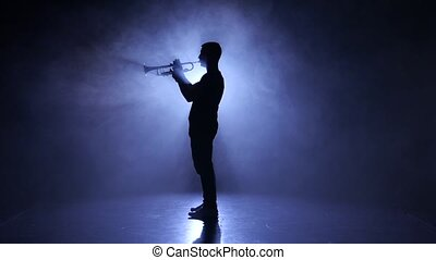 Professional musician in smoky studio playing on wind instrument, silhouette