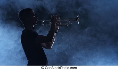 Professional musician man playing on trumpet. Smoky isolated studio, silhouette