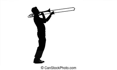 Professional musician playing on trombone in slow motion. Black silhouette