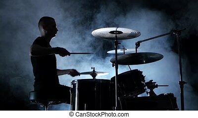 Professional musician plays music on drums . Smoky background. Side view. Silhouette. Back light. Slow motion