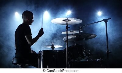 Professional musician plays music on drums . Smoky background. Side view. Silhouette. Back light