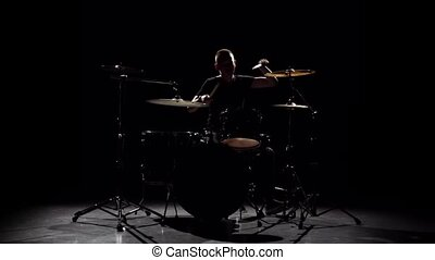 Professional musician plays music on drums with the help of sticks. Black background. Silhouette. Slow motion