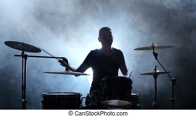 Professional musician plays music on drums with the help of sticks. Smoky background. Silhouette
