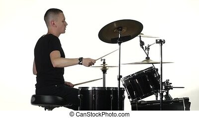 Professional musician plays music on drums with the help of sticks. White background. Side view. Slow motion
