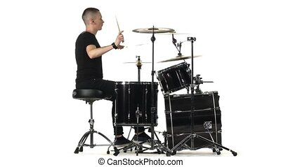 Professional musician plays music on drums with the help of sticks. White background. Side view