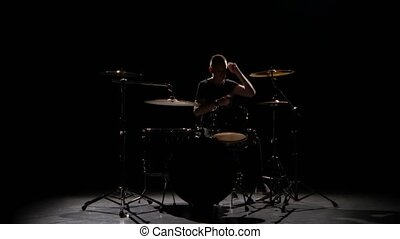 Professional musician plays music on drums with the help of sticks. Black background. Silhouette