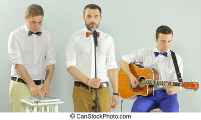Professional musicians united in a band perform in the studio on a white background