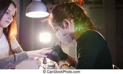 Professional nails care in process, cosmetician with mask in black gloves making nails female customer for a manicure with gel cover